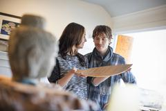 Smiling couple standing in a living room, woman holding a wooden tray. Stock Photos