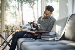 Man wearing a grey roll-neck jumper sitting on a sofa with a dog on his lap - stock photo