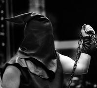 executioner with black hood on his head and the chain - stock photo