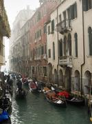 A view of a narrow canal crowded with boats and traditional gondolas Stock Photos