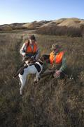 Two bird hunters out with shotguns and working retriever dogs Stock Photos