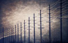 Power lines at regular intervals reaching into the distance - stock photo