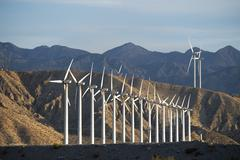 A group of wind power turbines in the sunset. - stock photo
