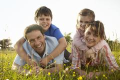 A family, two parents and two children outdoors on a summer evening. Stock Photos
