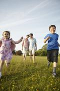 A family, two parents and two children outdoors in the summer. Stock Photos