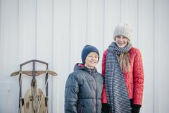 A brother and sister side by side in a yard in winter. Stock Photos