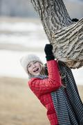 A young girl in a red jacket, and long scarf, gripping a tree trunk. Stock Photos