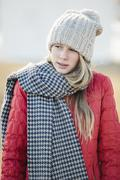 Stock Photo of A girl in a red jacket with a large checked woollen scarf.