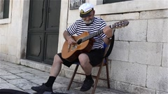 A male street musician playing guitar and singing in the old town - stock footage