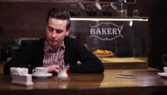 Young man waiting at a cafe, a little nervous, looking at his watch - stock footage
