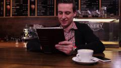 A young man in a cafe, sitting at the table with tablet PC, typing something Stock Footage
