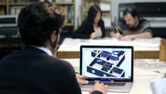 architect using cad software: colleagues working on blueprints in background - stock footage