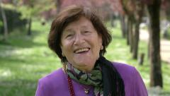 happy old woman laughing and smiling in the park - stock footage