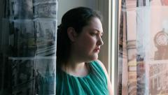 Depressed overwheight woman looking out the window Stock Footage