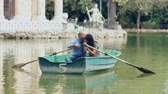 people in love on rowboat: couple falling in love on a little lake in Rome - stock footage