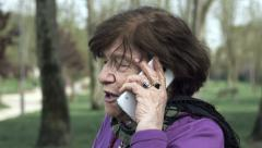Angry old woman talking a the mobile phone: troubled phone call, anger Stock Footage