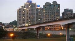 Metro train passes bridge against building facades, twilight time Stock Footage