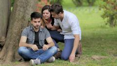 sad young man is helped and comforted by his friends - stock footage
