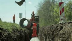 Placing concrete pipes in channel,dredge digging in background,road construction Stock Footage