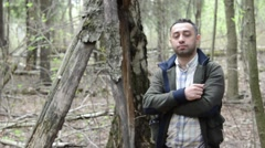 Youn Man standing in the woods looking at the camera Stock Footage
