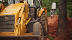JCB Bulldozer tractor digging soil with Indian worker in background 3 Stock Footage