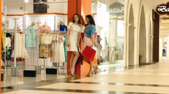 Two young woman talking near by shop entrance Stock Footage