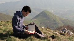 Write in your journal your thoughts on a mountain top Stock Footage