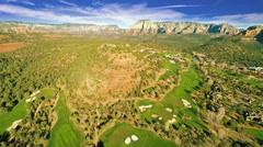 Aerial footage of a golf course and surrounding Red Rocks in Sedona, Arizona - stock footage
