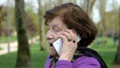 Old woman at the park is having a mobile phone call Stock Footage
