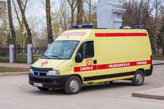 """Ambulance car parked up in the street. Text on russian: """"Acute care"""" - stock photo"""