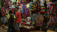 Men at street stand with colorful clothes in the night time in Goa. Stock Footage