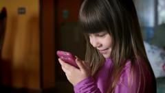 Cute girl playing with a modern smartphone: little girl using mobile phone Arkistovideo