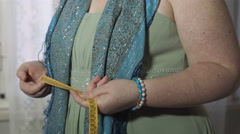 Overweight woman standing sad and pensive with a measurement tape in her hands Stock Footage