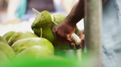 Street vendor cutting a Coconut and pouring fresh Coconut water Stock Footage