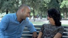 Couple falling in love and plying the game of love on the bench in a park Stock Footage