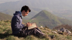 Stock Video Footage of Read a book in solitude on the mountain top