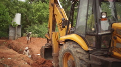 JCB Bulldozer tractor digging soil with Indian worker in background 6 Stock Footage