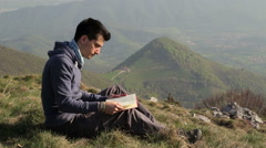 Boy reads book sitting in the grass in front of a beautiful landscape Stock Footage