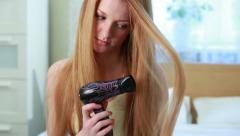 Charming young red-haired woman dries the hair dryer her long hair. Stock Footage