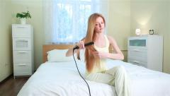 Young woman with long red hair uses a Curling iron for straightening hair. Stock Footage