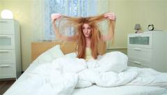A young woman can not comb his terribly confusing red hair. Dolly shot. - stock footage