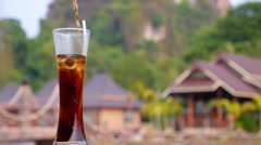 Refreshing Cocktail with Cola in a Tall Glass Outdoors Stock Footage
