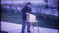 2025 - young carpenter nails birdhouse together - vintage film home movie Stock Footage