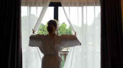 Woman in Bathrobe Opening Window Curtains at Hotel Room Stock Footage