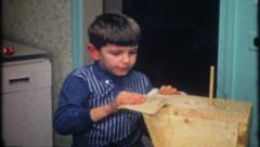 2026 - young boy sandpapers birdhouse before painting - vintage film home movie Stock Footage