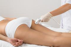 Close-up Of Woman Lying Receiving Epilation Laser Treatment On Buttock Stock Photos