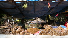 Vendor behind a street stand with local food products. Stock Footage