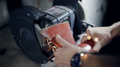 Close up the hands of a blacksmith sharpening axe on electrical grinder Stock Footage
