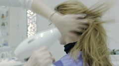 Hairdresser drying hair with blow dryer of woman client at beauty parlour Stock Footage