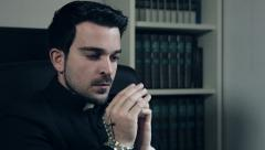 Catholic priest starting praying with a rosary in his hands Stock Footage